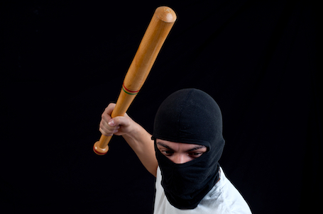 masked man swinging a bat